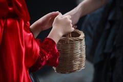 La main rouge de fantaisie d'enfant de habillage de costume de capot livrent le panier en bois tissé à la sorcière noire dans le  images libres de droits
