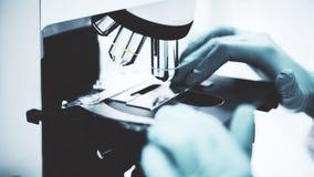 La main s de scientifique dans un manteau de laboratoire est prête pour commencer une recherche de microscope dans un laboratoire photo libre de droits