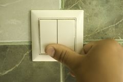 La main s'?teint la lumi?re dans la salle de bains utilisant un commutateur de mur photo libre de droits