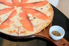 La main saumonée de pizza font est goûtée images stock