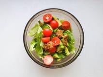 La main serre la chaux au-dessus de la salade végétarienne est faite à partir de l'avocat, des tomates, du concombre et du basili image libre de droits