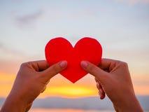 La main soulève le coeur de papier rouge avec la lumière du soleil de tache floue pendant le coucher du soleil, jour de valentine Image libre de droits