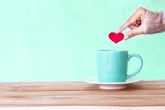la main tenant la forme rouge de coeur a mis dans une tasse de tasse de café sur le woode Photo libre de droits