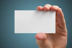 La main tenant la carte vierge blanche de visite d'affaires, cadeau, billet, passage, présentent d'isolement sur le fond bleu Cop Photo libre de droits