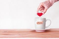 la main tenant la forme rouge de coeur a mis dans une tasse de tasse de café avec le hasard Photos stock