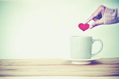 la main tenant la forme rouge de coeur a mis dans une tasse de tasse de café sur le woode Image stock