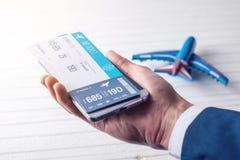 La main tenant le téléphone avec les billets d'avion Concept d'achat en ligne et réservation des billets pour le voyage Photos stock