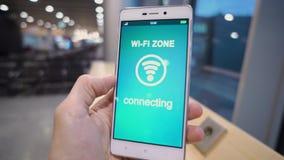 La main tenant le téléphone intelligent avec la zone de wifi se connectent l'écran au-dessus du fond de tache floue, des affaires banque de vidéos
