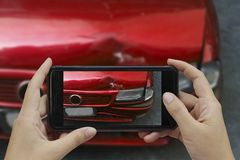 La main tenant le téléphone intelligent prennent une photo à la scène des cras d'une voiture photographie stock libre de droits