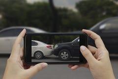 La main tenant le téléphone intelligent prennent une photo à la scène des cras d'une voiture images libres de droits