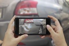 La main tenant le téléphone intelligent prennent une photo à la scène des cras d'une voiture image libre de droits