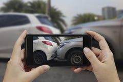 La main tenant le téléphone intelligent prennent une photo à la scène des cras d'une voiture photo stock