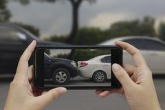 La main tenant le téléphone intelligent prennent une photo à la scène des cras d'une voiture image stock