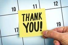 La main tenant la note de papier jaune avec des mots vous remercient Image stock