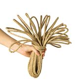 La main tient la corde de jute d'écheveau comme bouquet d'isolement sur le fond blanc photographie stock