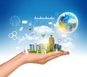La main tient la ville des gratte-ciel sur l'herbe verte et Photo stock