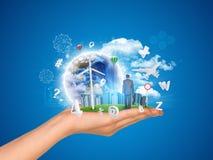 La main tient la ville des gratte-ciel sur l'herbe verte et Photos stock