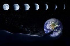 La main tient le globe à l'arrière-plan toutes les phases de la lune images libres de droits