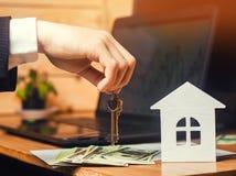 La main tient les clés sur la maison Concept des immeubles vente ou location du logement, location d'appartement realtor images libres de droits