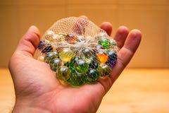 La main tient les marbres en verre colorés dans le filet Image stock