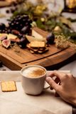 La main tient la tasse de café avec la nourriture à l'arrière-plan Photos libres de droits