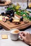 La main tient la tasse de café avec la nourriture à l'arrière-plan Photographie stock