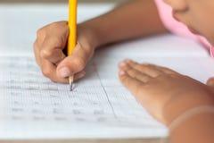 La main tient un crayon jaune et écrit dans un carnet photographie stock libre de droits