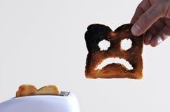 La main tient un découpe en tranches du pain grillé brûlé Images libres de droits