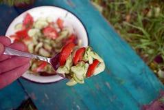 La main tient une cuillère de fer avec de la salade végétale au-dessus de la table et d'un plat Photos libres de droits