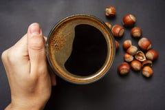 La main tient une tasse de café chaud avec la mousse contre la noisette image libre de droits