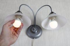 La main tord l'ampoule menée dans une lampe sur le mur blanc Photographie stock