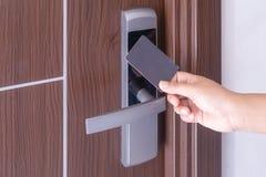 La main utilisant la carte principale sans contact futée électronique pour ouvrent la porte dans l'hôtel ou la maison image libre de droits