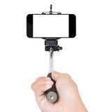 La main utilisant le bâton de selfie a isolé le chemin de coupure blanc à l'intérieur photos libres de droits