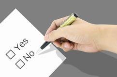 La main utilisant un stylo classique décident au choix oui ou non Photographie stock
