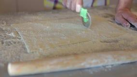 La main utilise un couteau de pizza pour des coupes la pâte banque de vidéos