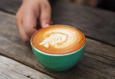 La main womeen avec du café de cappuccino dans une tasse verte sur en bois Images libres de droits