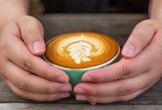 La main womeen avec du café de cappuccino dans une tasse verte sur en bois Photographie stock