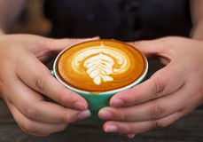 La main womeen avec du café de cappuccino dans une tasse verte sur en bois Images stock