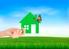 La maison à disposition sur le fond naturel vert Images stock