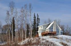 La maison au-dessus de la neige a couvert la côte Photographie stock libre de droits