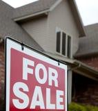 La maison avec a à vendre signent dedans la cour Photo libre de droits