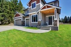 La maison d'American d'artisan avec des roches équilibrent, garage et porche concret de plancher image stock