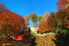 La maison de campagne en soleil d'automne comme feuilles tournent l'orange Image libre de droits