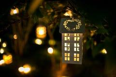 La maison de chandelier sur l'arbre dans le nigth avec la tache floue s'allume Photographie stock libre de droits