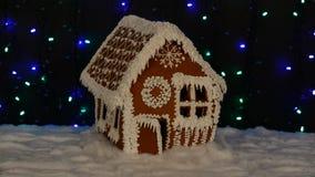 La maison de pain d'épice mangeable fabriquée à la main, décoration de neige, fond de guirlande banque de vidéos