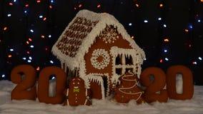 La maison de pain d'épice mangeable fabriquée à la main, 2020 inscription, petit homme, arbre de nouvelle année, décoration de ne banque de vidéos