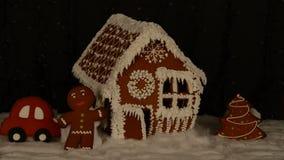 La maison de pain d'épice mangeable fabriquée à la main, petit homme, arbre de nouvelle année, voiture, décoration de neige, guir banque de vidéos