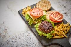 La maison deux grillée savoureuse a fait des hamburgers avec du boeuf, la tomate, l'oignon et la laitue image libre de droits