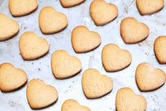 La maison a fait les biscuits en forme de coeur sablés sur le plateau de cuisson Image stock