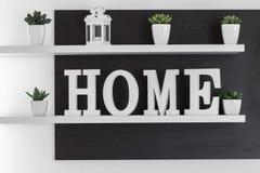 La maison marque avec des lettres le décor sur l'étagère blanche photographie stock libre de droits